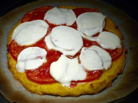 Tranches de mozzarella légèrement fondues sur la pizza sans gluten